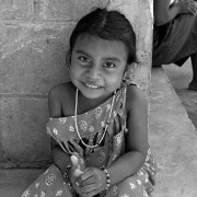 A 4-year-old smiling indigenous girl wearing a string of beads, smiles while sitting outside her home.