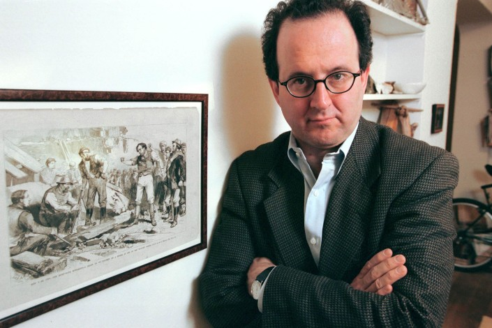 Jonathan Tasini, arms crossed, stands next to a lithograph of a late 19th century lithograph of a workers' protest.