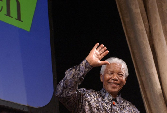 A smiling Nelson Mandela, waves to children at the Manhattan Center in New York City.