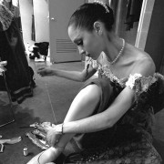 A ballerina dressed in pearls and a lace costume, mends her ballet shoes with a needle and thread before a performance.