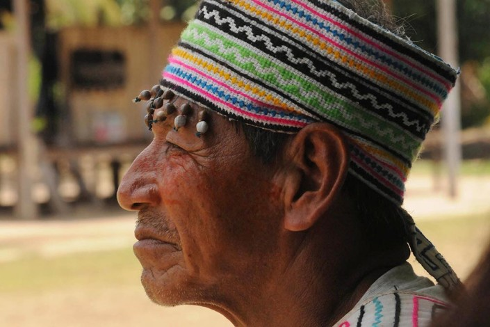 An indigenous Shipibo Conibo community leader, wearing a traditional, colorful and beaded head wrap, painted face and garment, stands outside the community center in Nuevo Saposoa, Peru.