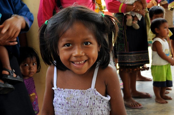 A smiling girl from the indigenous Shipibo-Conibo community of Nuevo Saposoa, stands with members of her community.