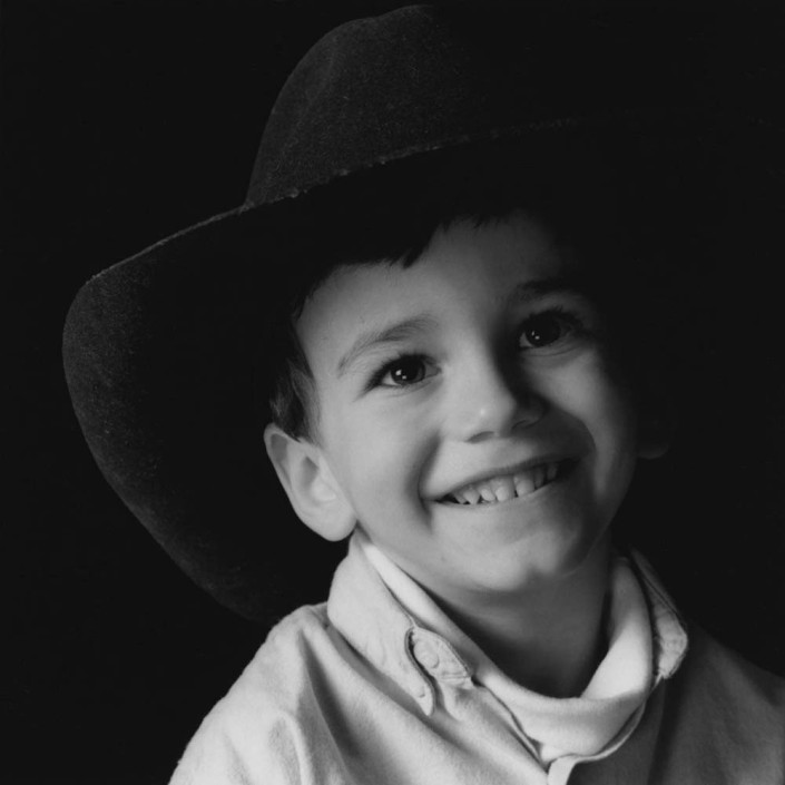 A small boy, wearing a cowboy hat many sizes too large, smiles during a portrait session.