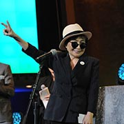 Yoko Ono, wearing a black and white fedora and black sunglasses, raises her hand in a peace sign as Hugh Jackman stands beside her.