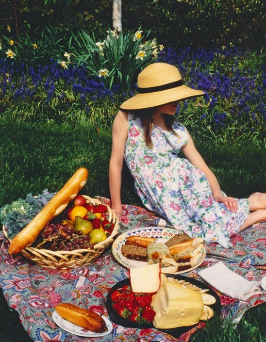 A girl in a garden, wearing a straw hat and floral dress sits on a picnic blanket filled with fresh breads, cheeses and fruits, for an illustration.