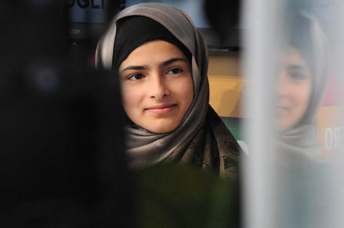 An image of youth activist Minahil Sarfraz, wearing a head scarf, reflected in a window, at UNHQ.