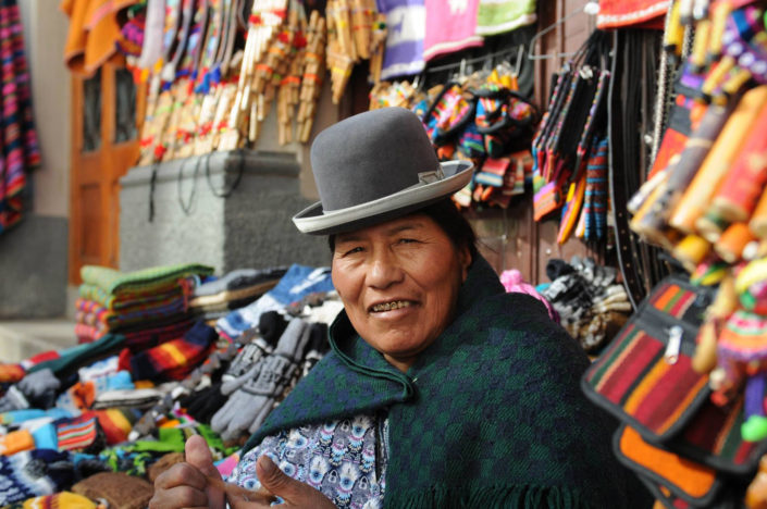 An indigenous woman wearing a bowler hat is surrounded by colorful textiles in La Paz, Bolivia.