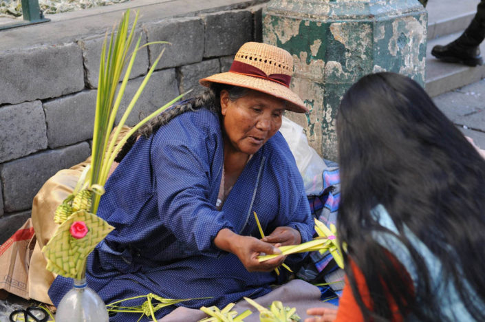 A woman wearing a straw hat sells decorative palm fronts in the shape of crosses on a street in La Paz, Bolivia.