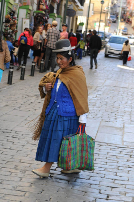 An indigenous woman wearing a traditional bowler hat and pollera (pleated skirt with petticoat), walks down the cobblestoned street Calle Sacarnaga in La Paz, Bolivia, on May 1, 2014.