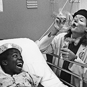A young patient is entertained by the Clown Care Unit of the Big Apple Circus in his hospital room.