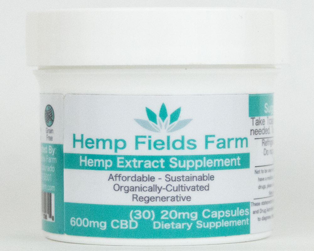 A white, short jar with a teal and white label containing CBD capsules.