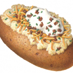 Baked potato with the works: butter, sour cream, chives, cheddar cheese and bacon bits