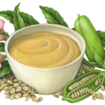 Sesame tahini paste in a white bowl with a sesame plant.