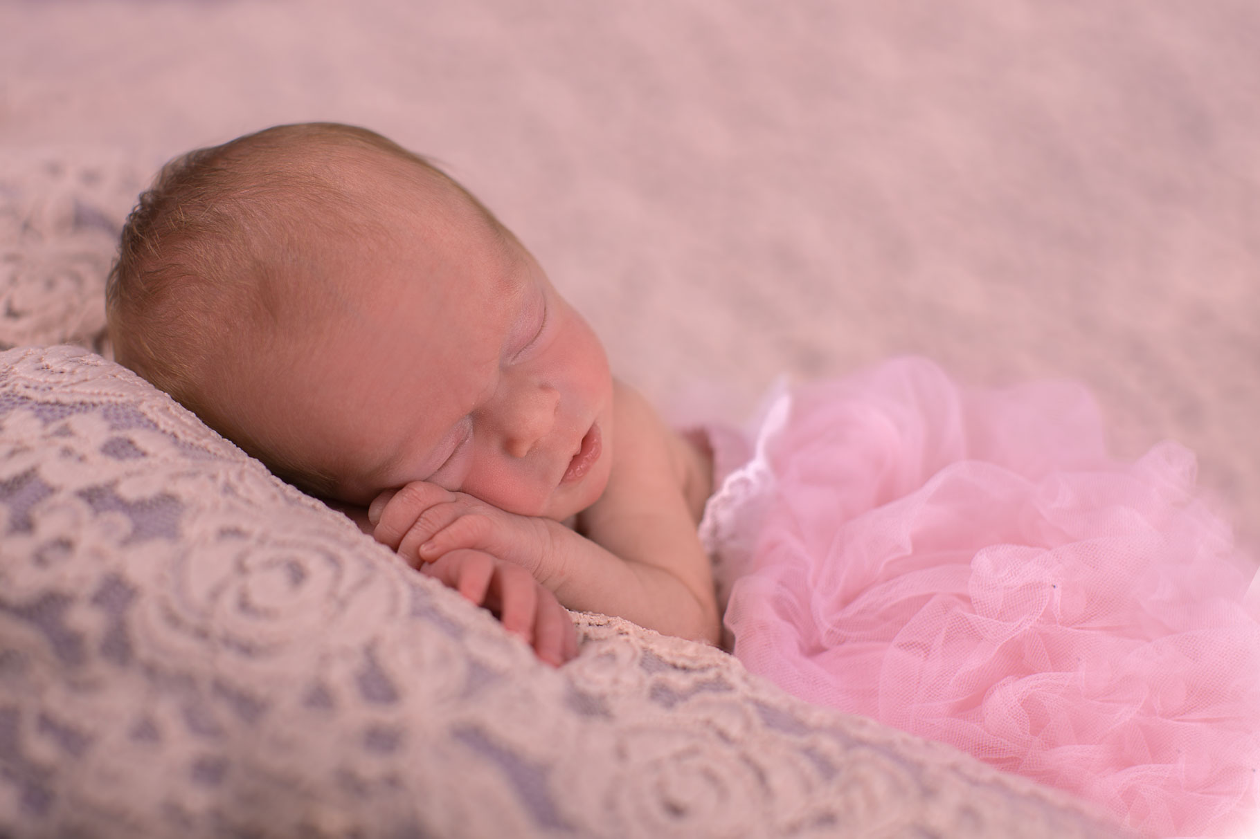 Image of baby girl asleep with her head on her hands
