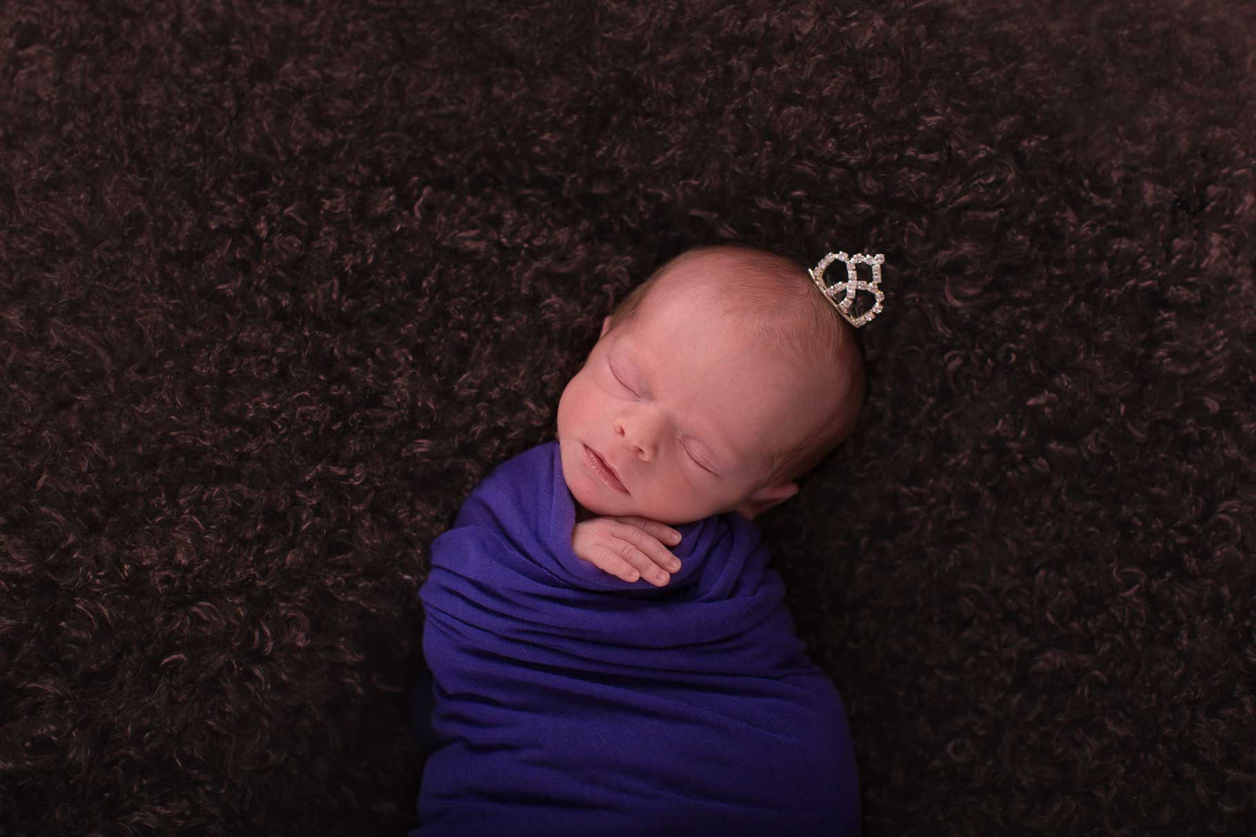 Image of baby swaddled with her hand sticking out