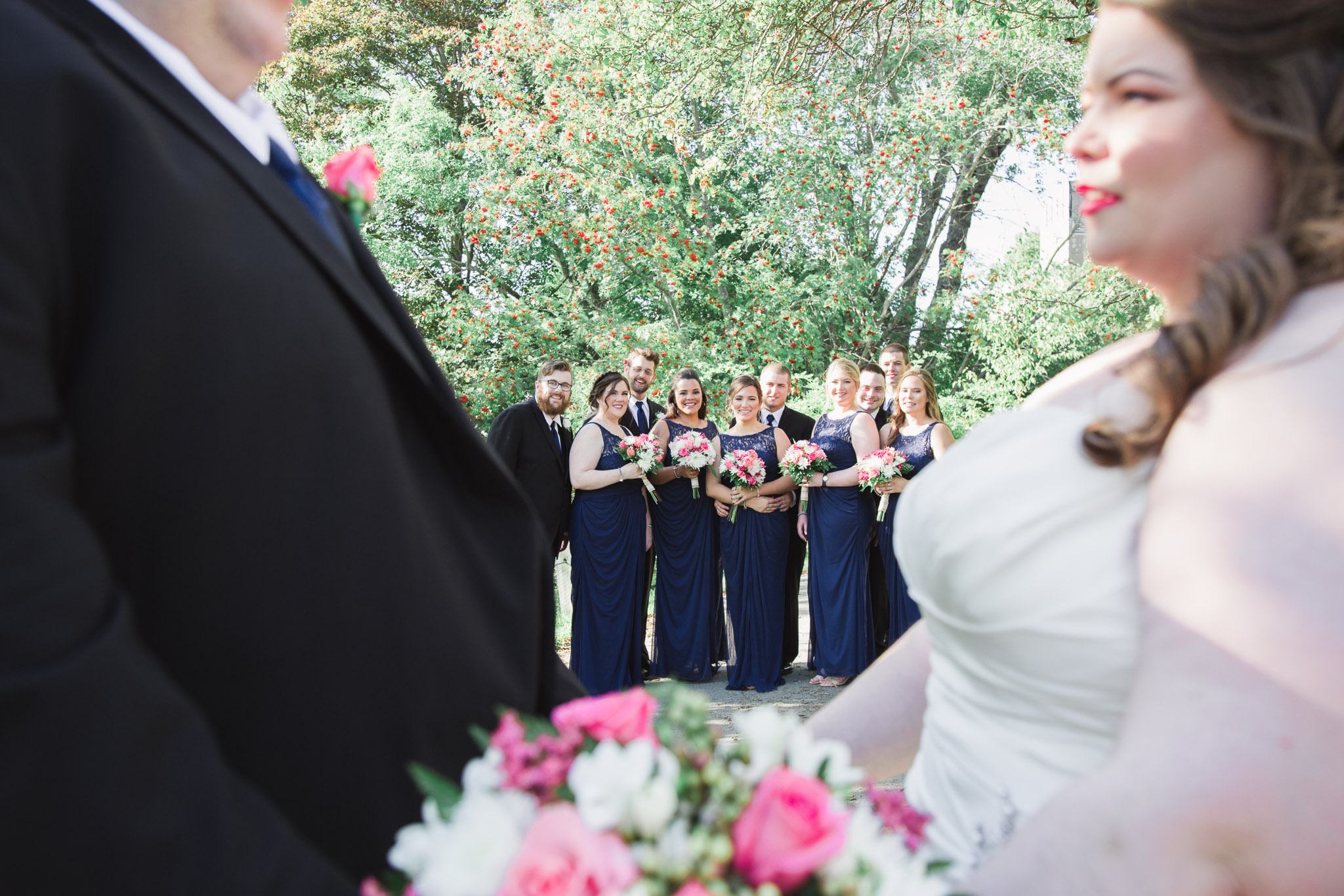 Image of bride and groom looking at each other with bridal party posing at the background