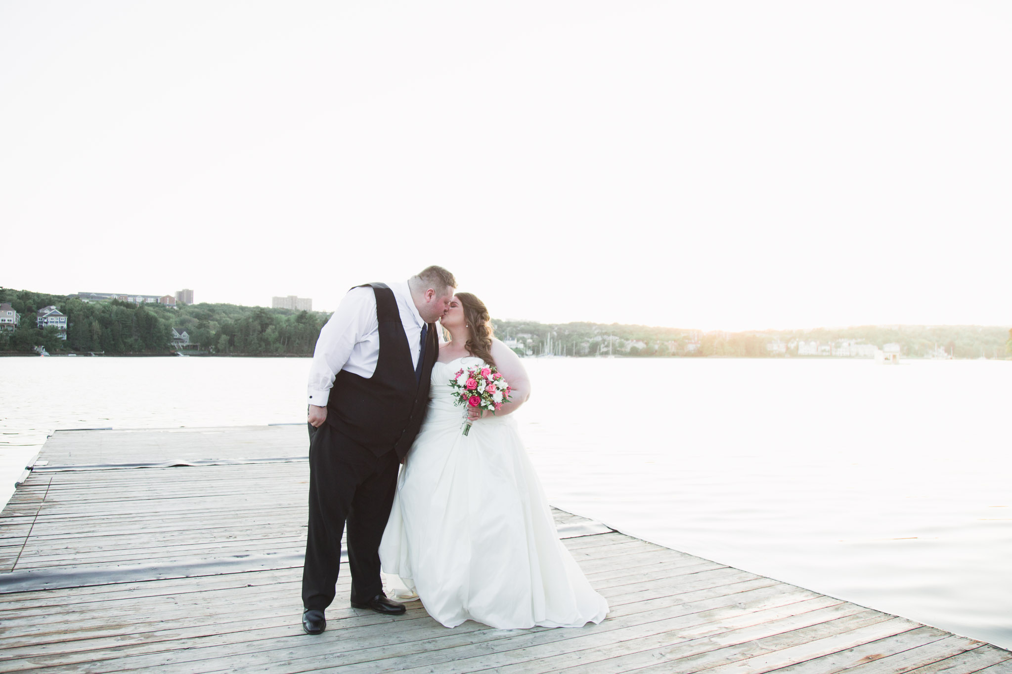 Bride and groom standing on the dock and kissing
