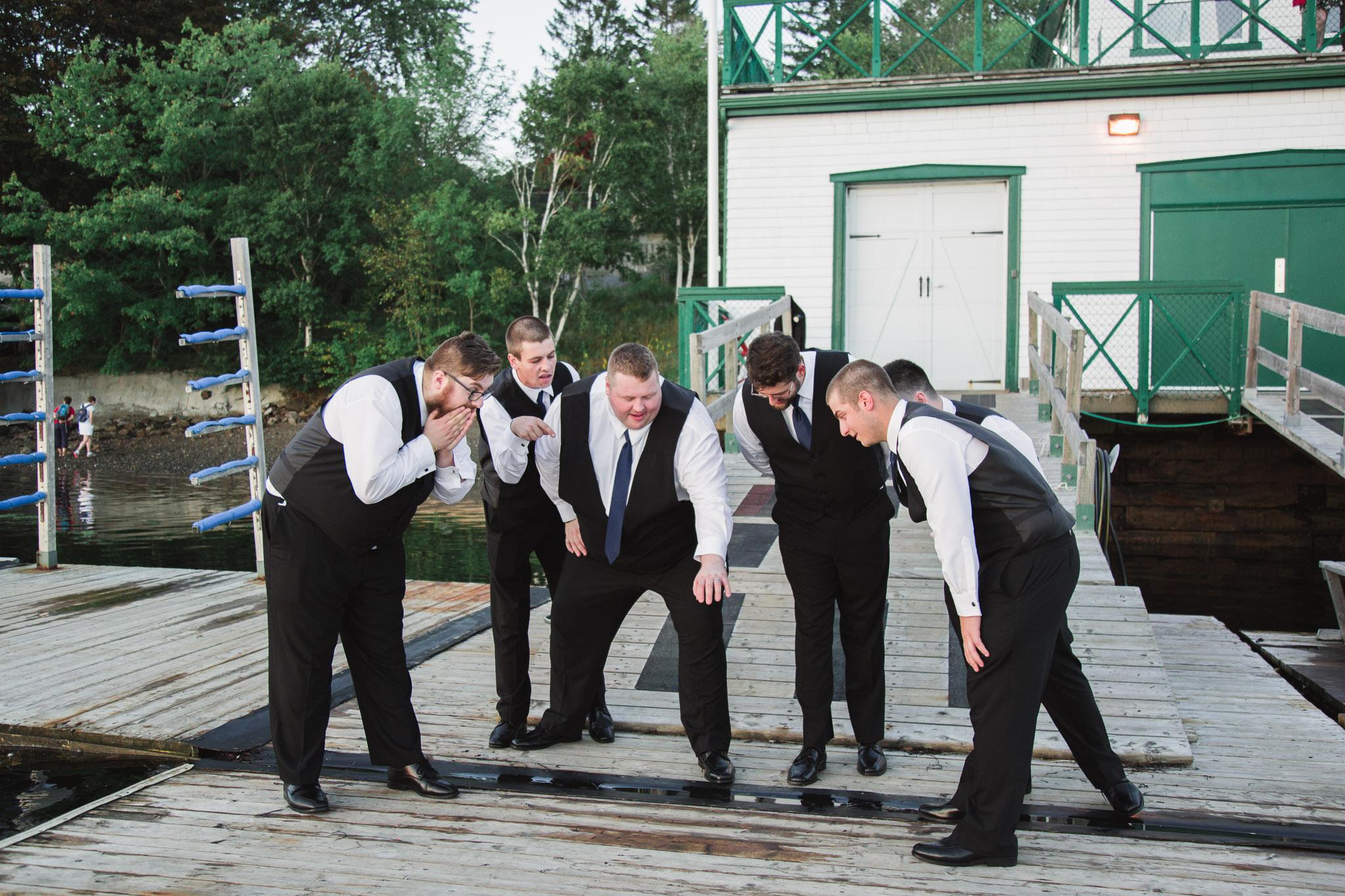 Image of groom and groomsmen looking at grooms ring