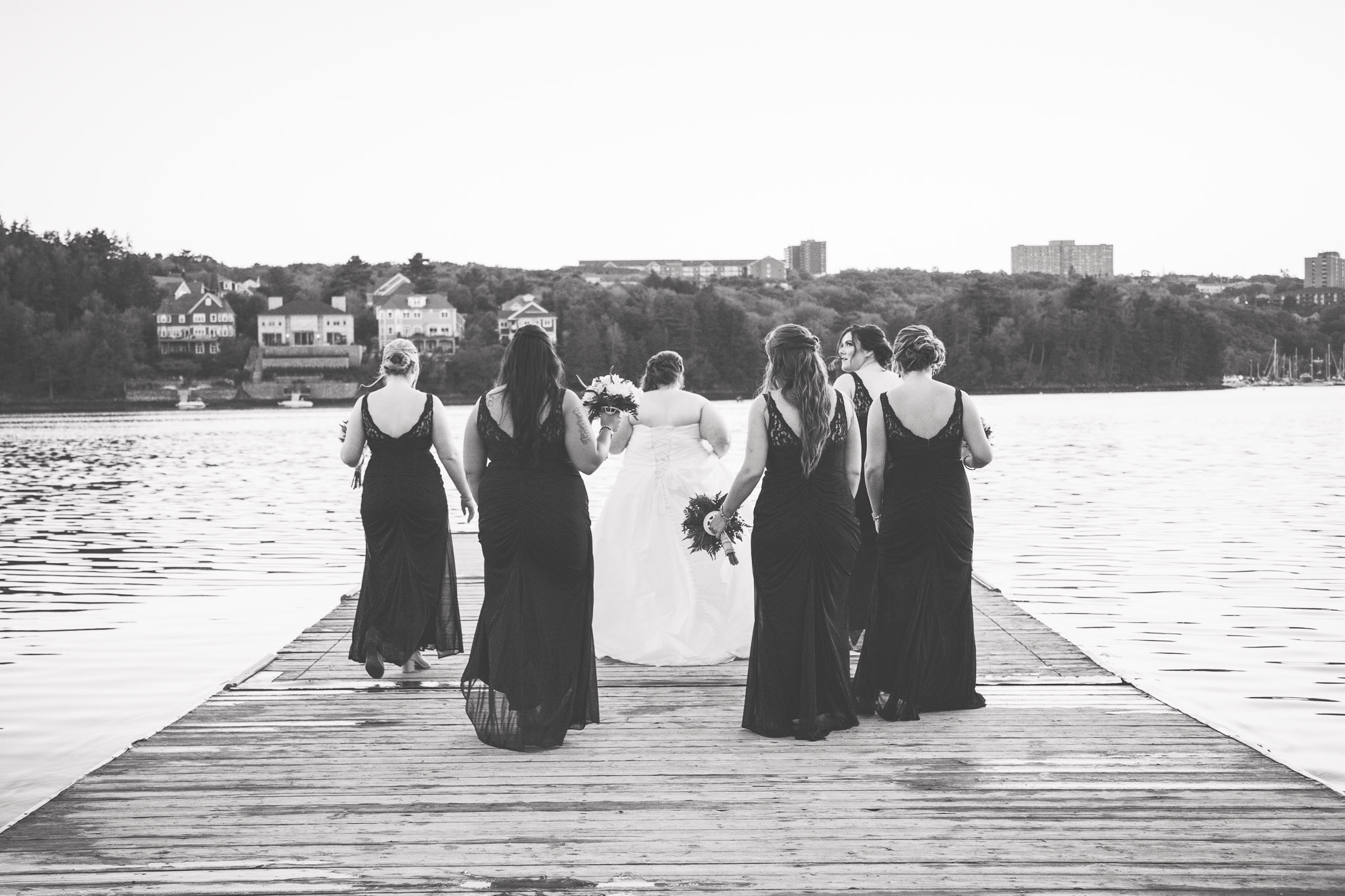 Image of bride and bridesmaids walking away on Saint Mary's boat club dock