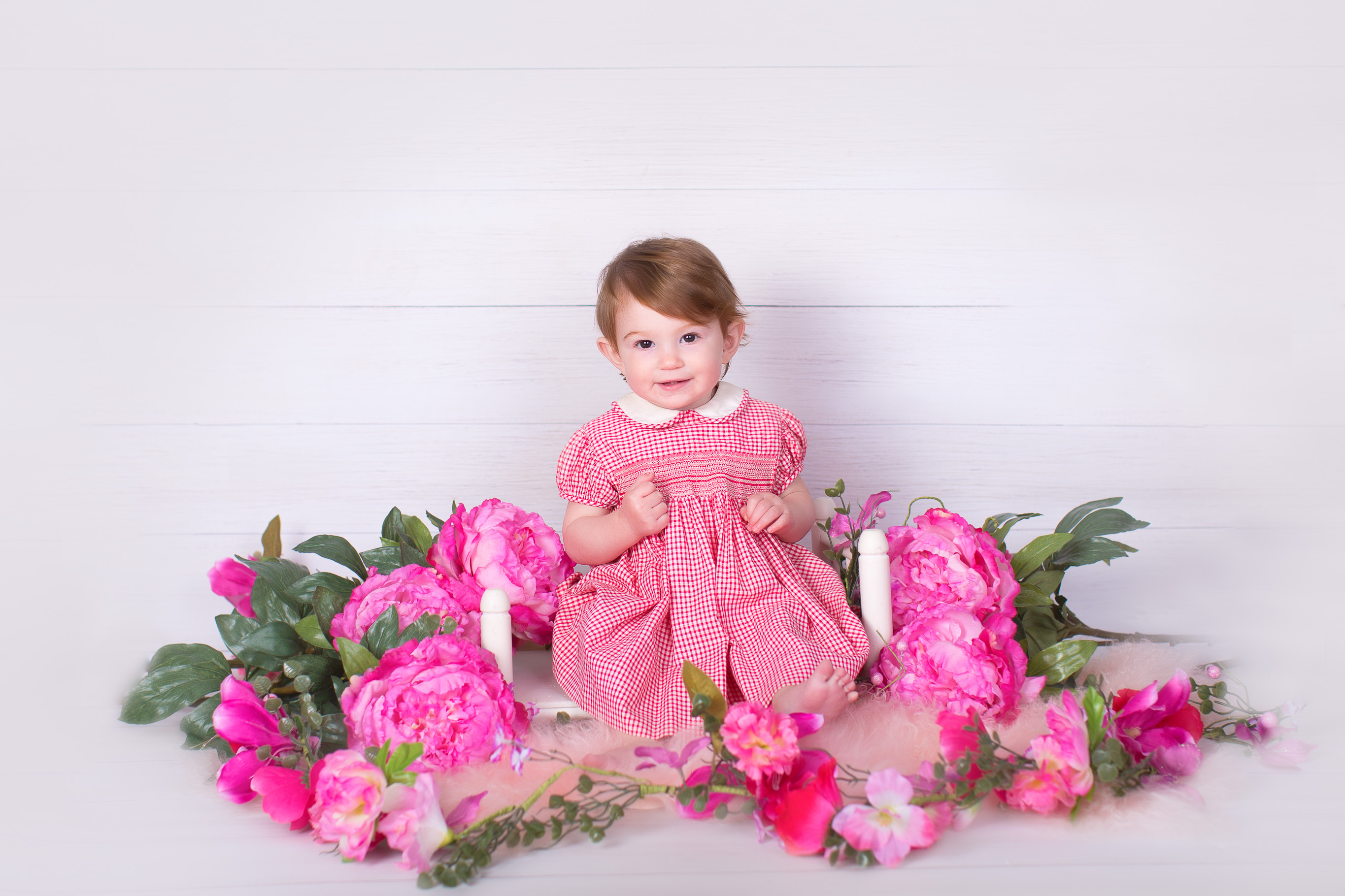 Image of little girl in pink dress posing for first birthday session with pink flowers around her