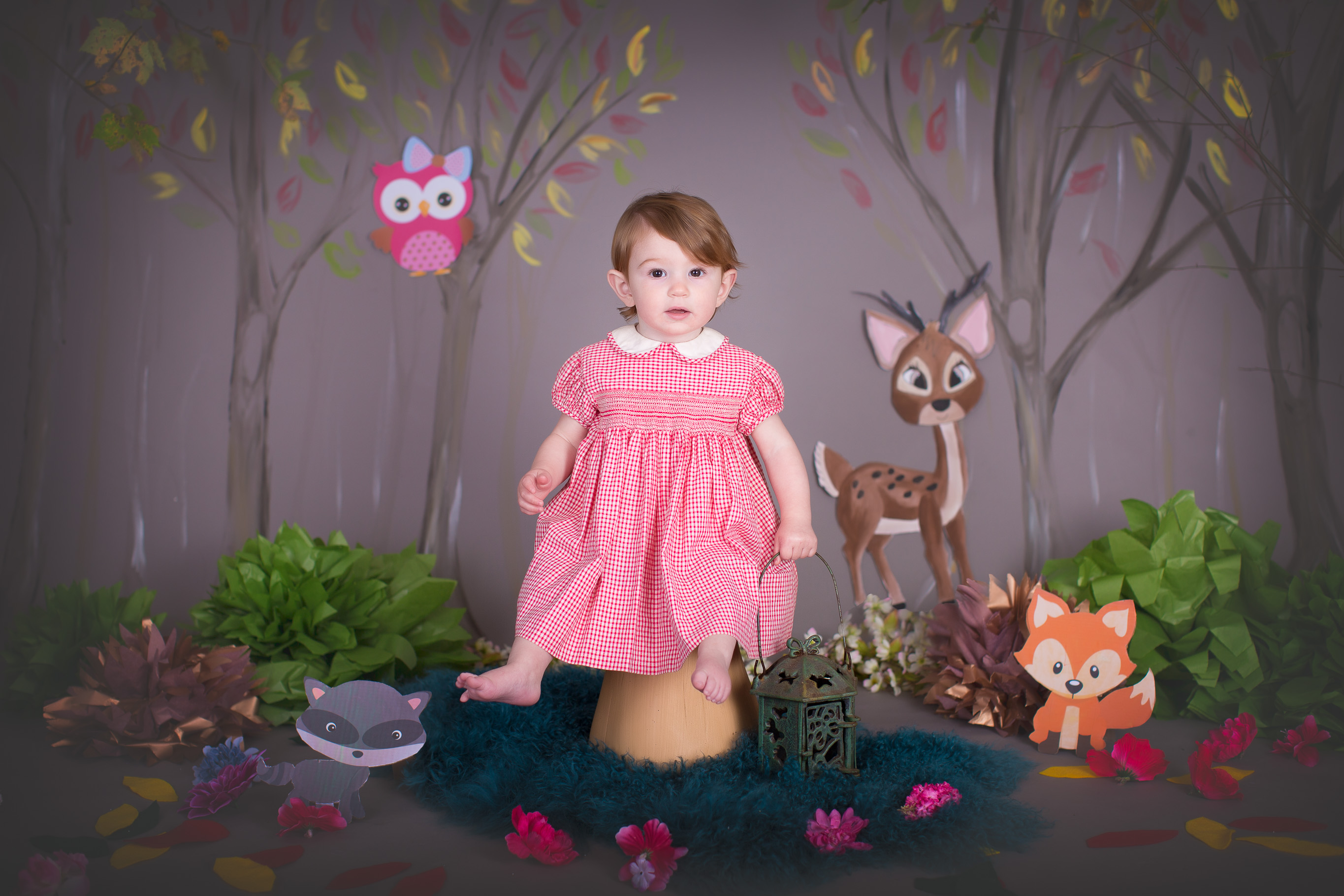 Image of little gild sitting on stool surrounded by painted woodland scene