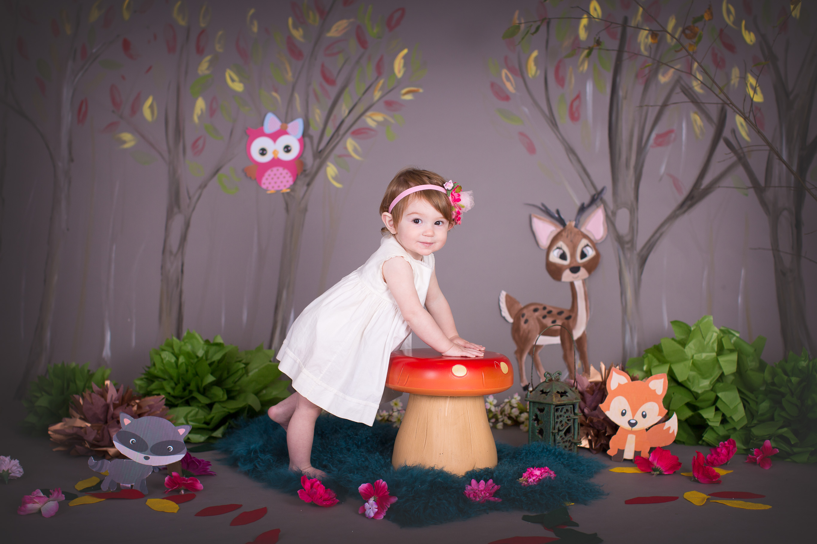 Image of little girl wearing white dress leaning on toadstool surrounded by woodland cake smash set up