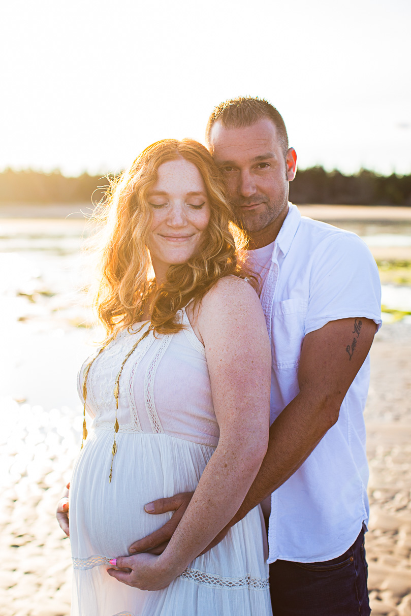 Image of expecting couple standing close on the beach