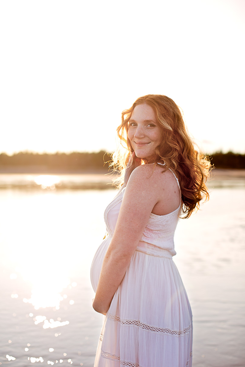 Image of pregnant woman wearing white dress standing in the water