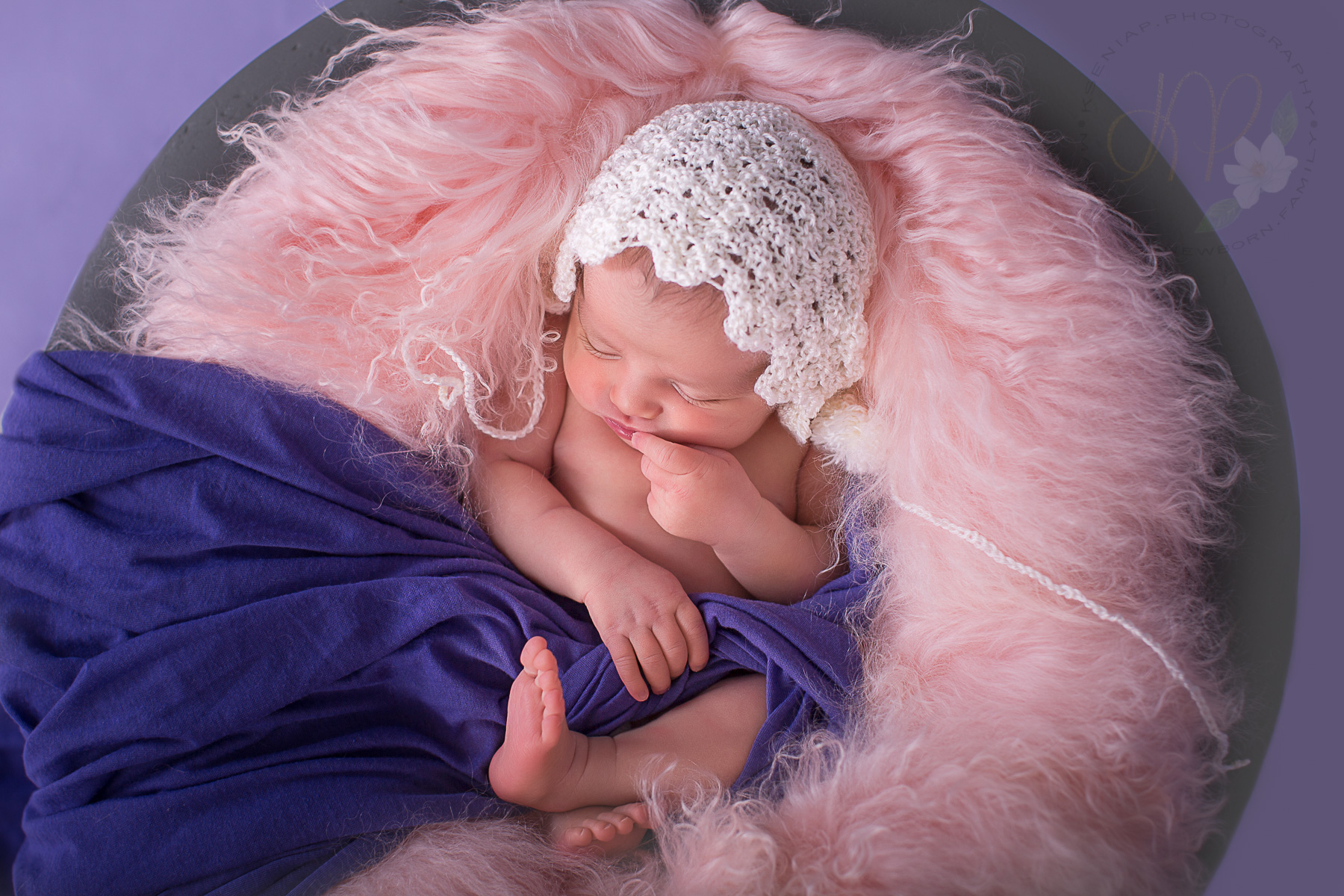 Image of newborn baby wearing a white hat and wrapped in purple wrap asleep