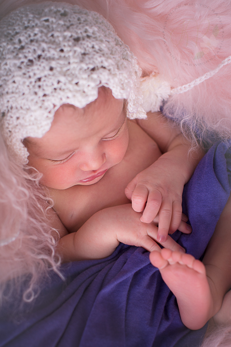 Image of asleep baby wearing a hat during newborn photosession
