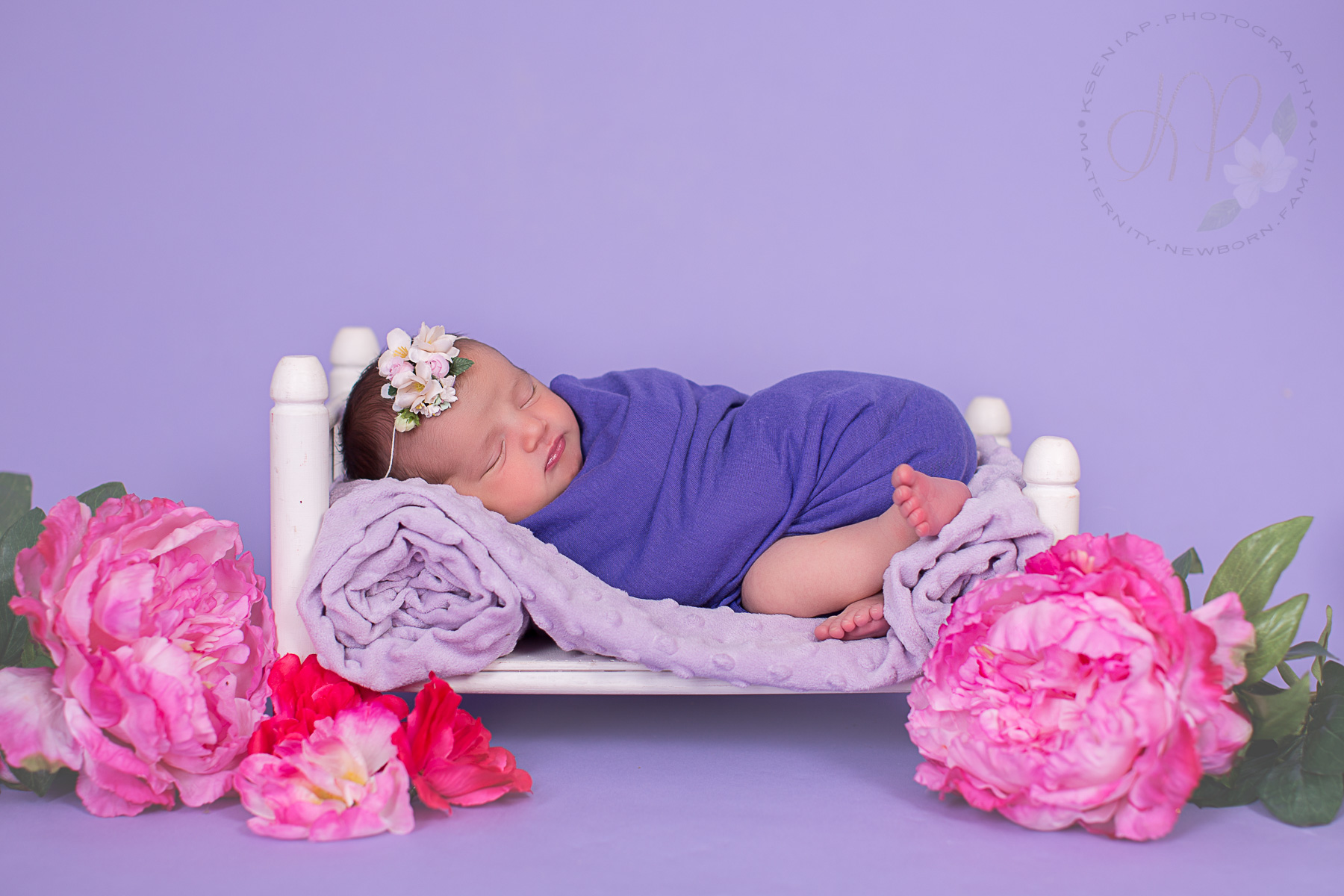 Image of baby wrapped up in purple wrap and asleep on a prop bed with flowers around it.