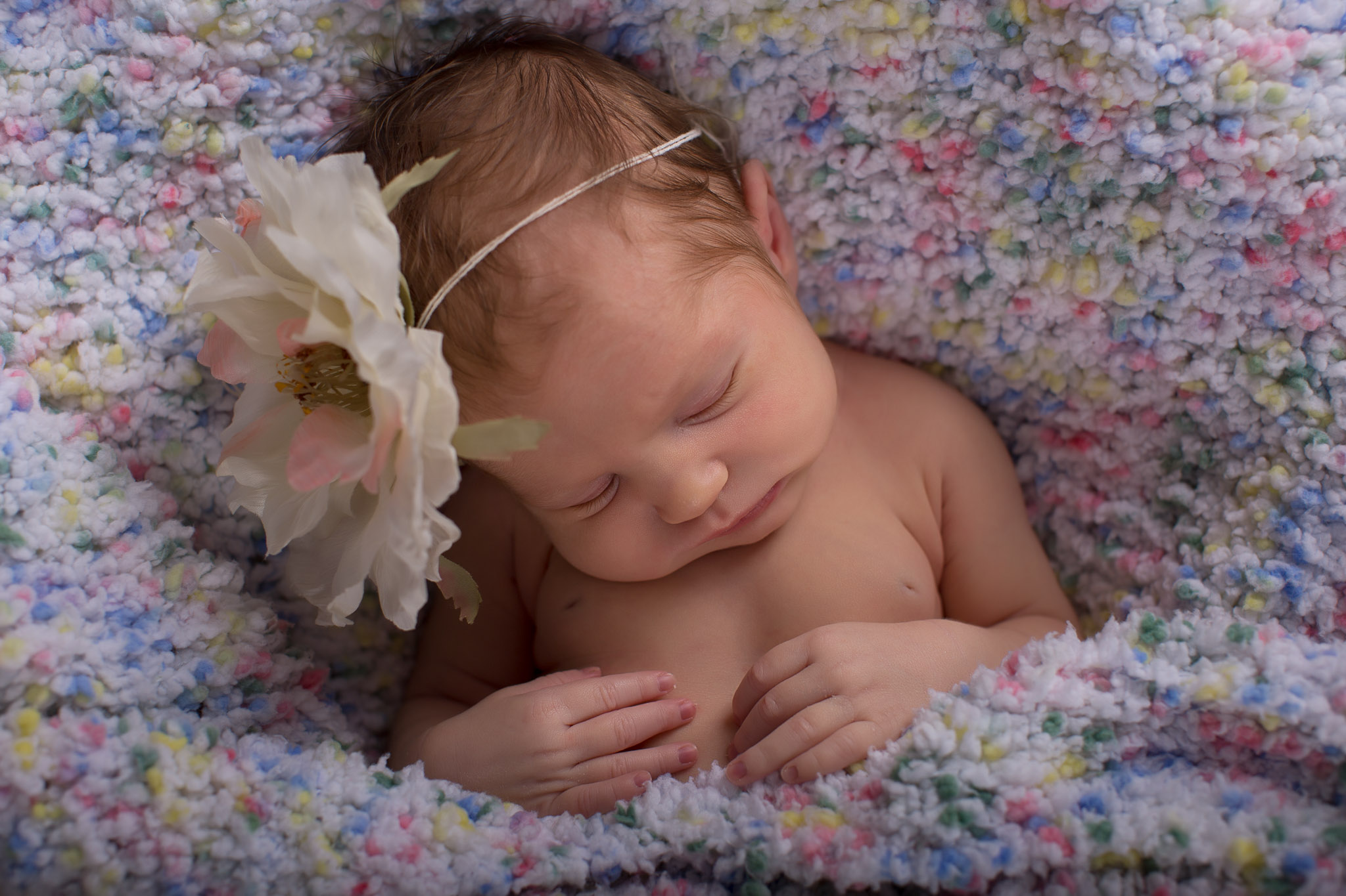 Image of newborn baby sleeping with big flower headband on her head