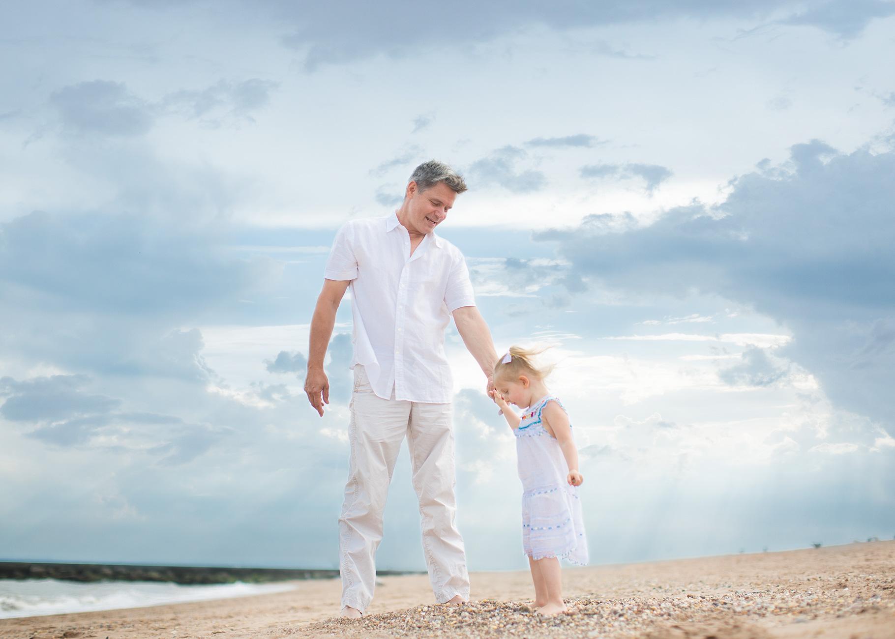 Man at the beach holding girls hand