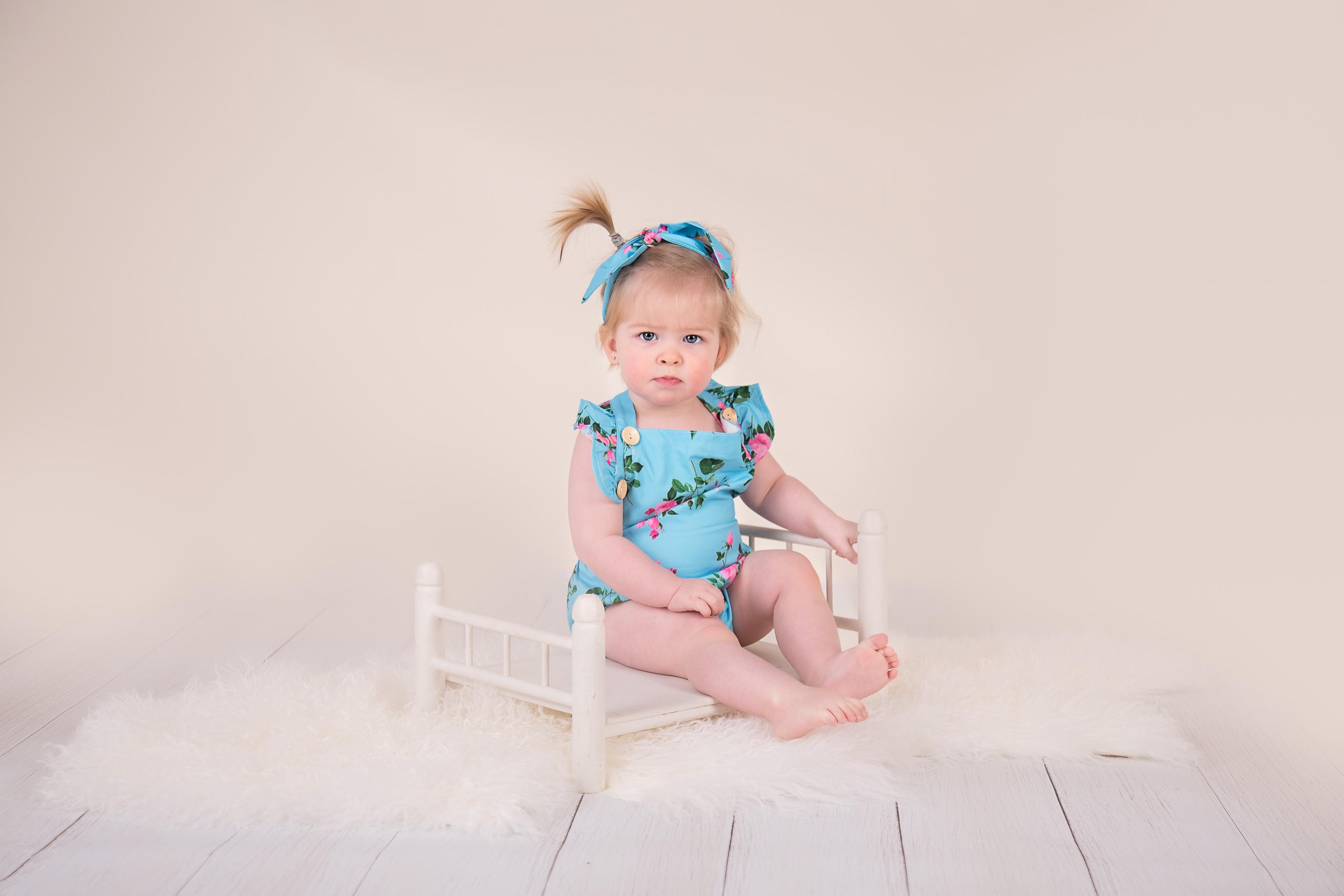 little girl sitting on prop bed in blue romper