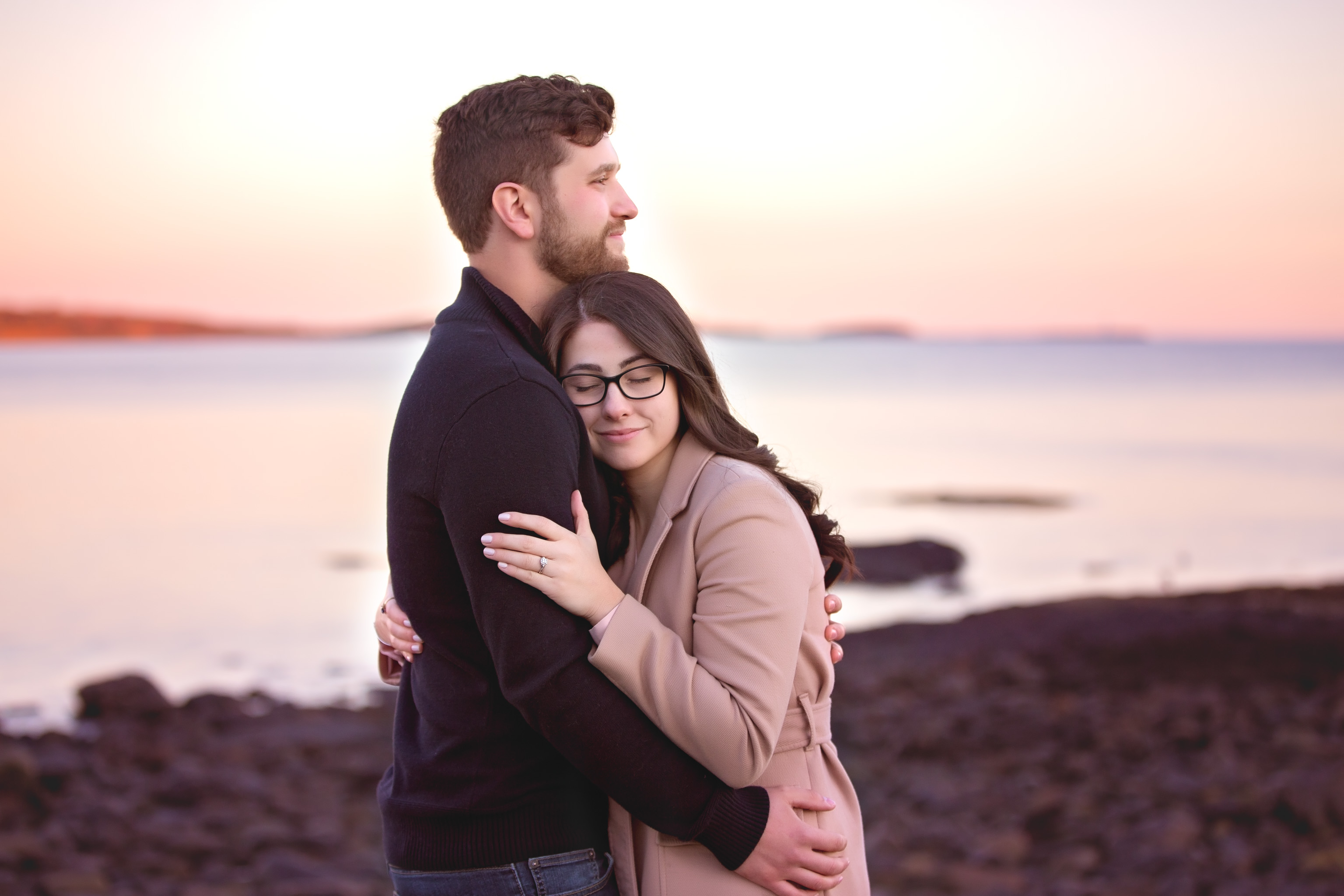 Couple embracing on the beach during engagement session