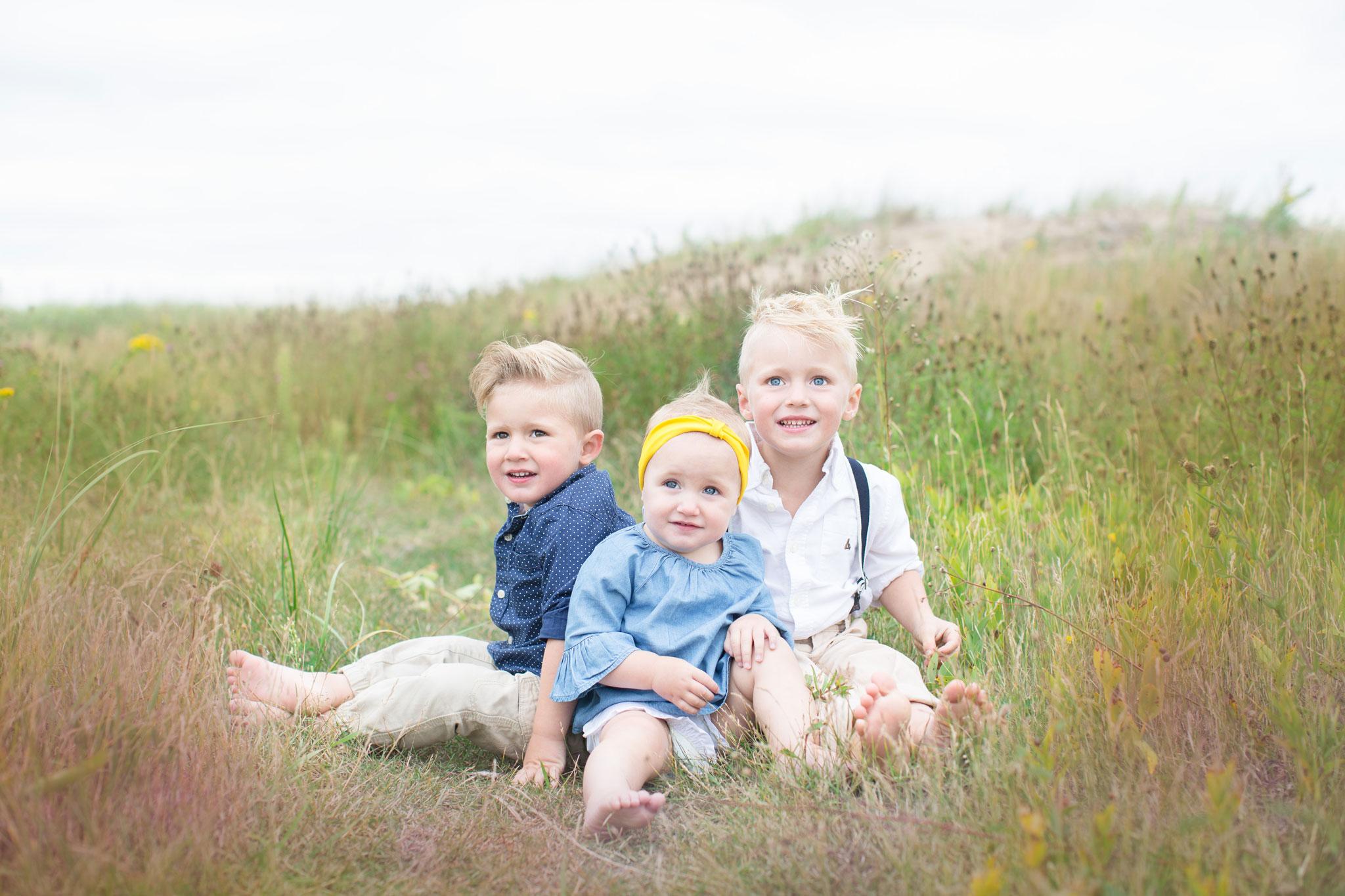 Three children sitting in the field of grass
