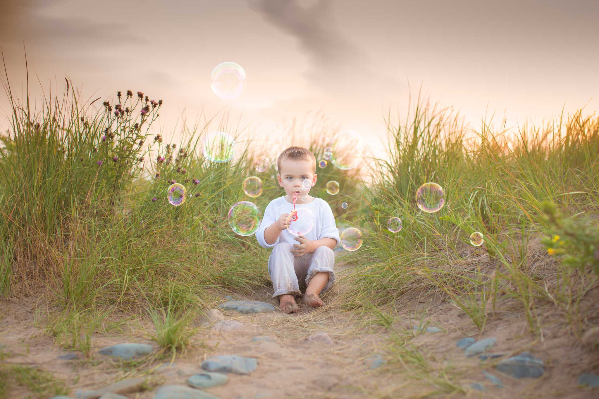 Boy blowing bubbles during evening at the beach