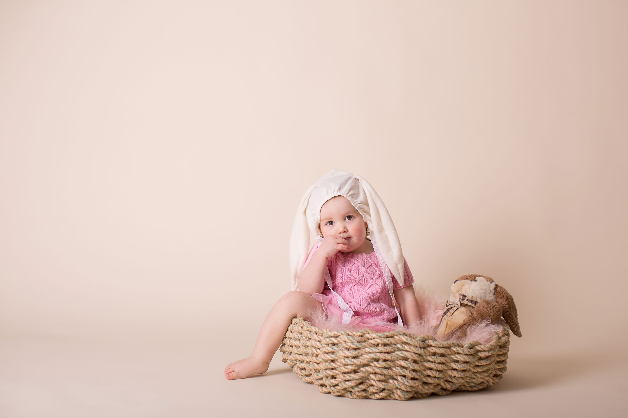 Girl wearing bunny hat with ears sitting in the basket