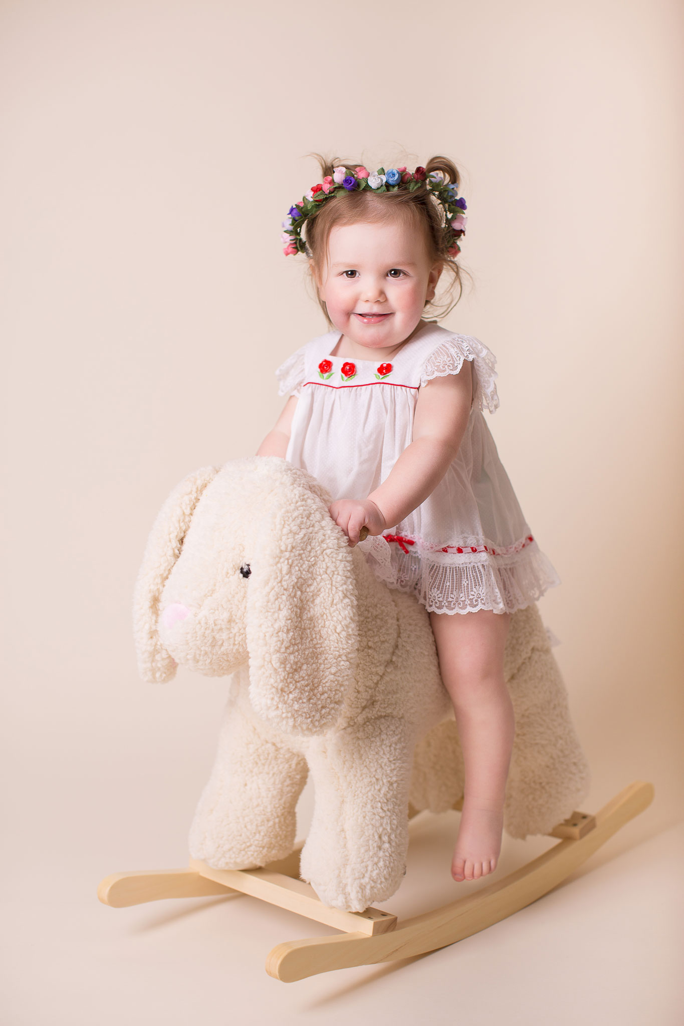 Girl sitting on rocking lamb with flower headband in her head