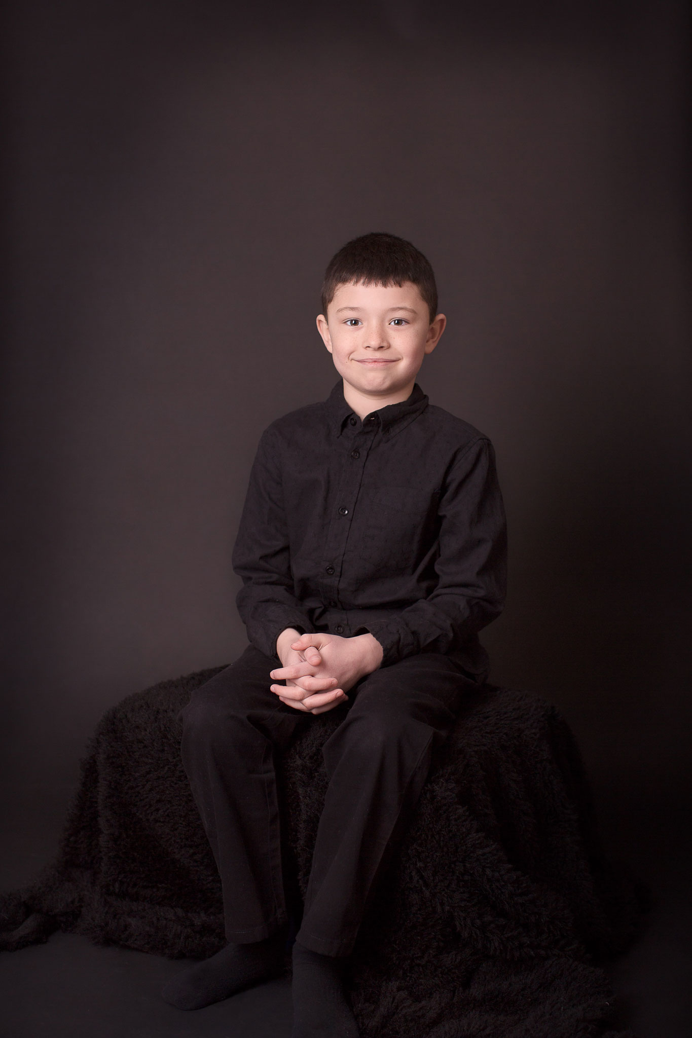 Boy posing for portrait sitting on the bench