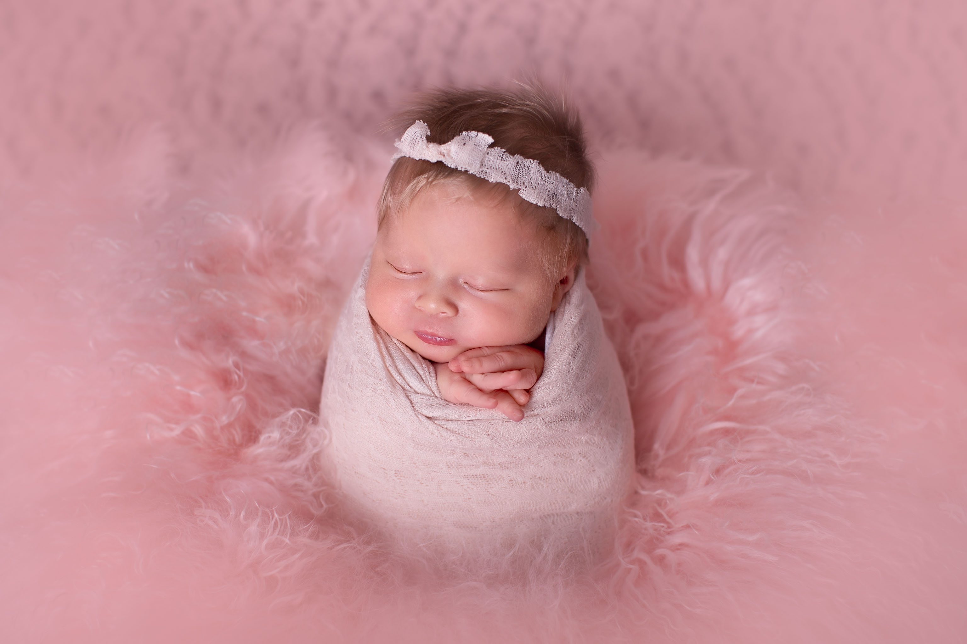Image of newborn baby girl wrapped up and posed for a newborn session