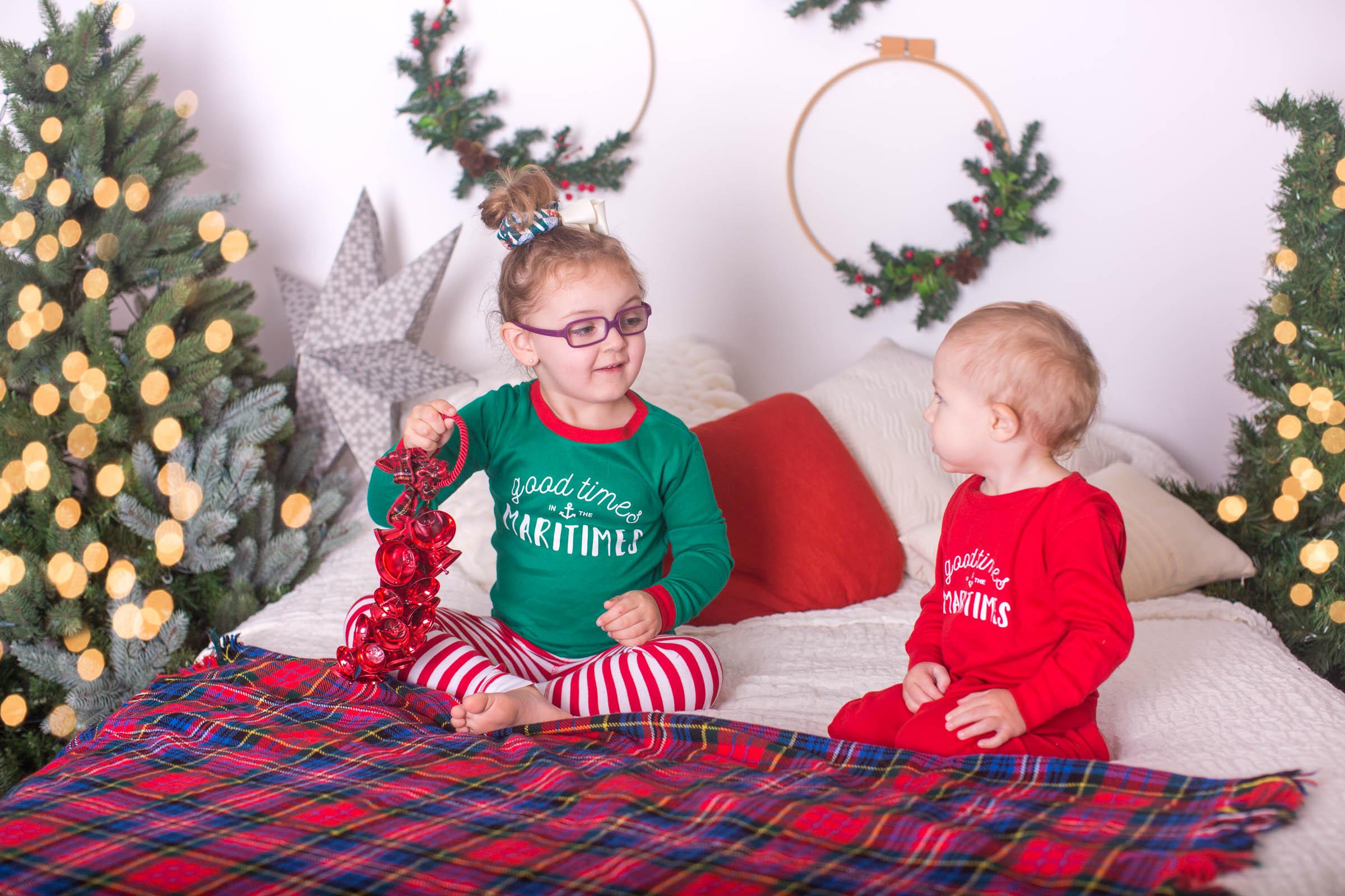 Image of 2 children dressed in Christmas pyjamas