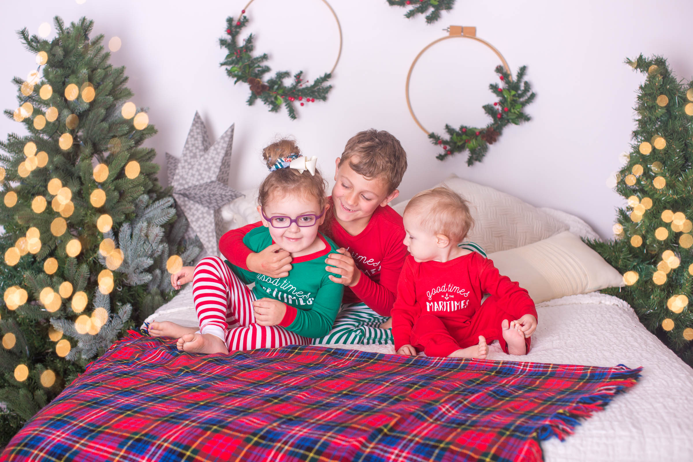 Image of 3 children sitting on bed during Christmas photoshoot