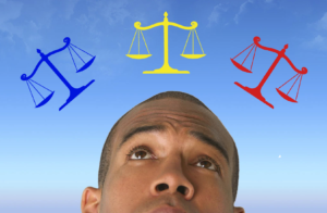 a man ponders over blue, yellow, and red legal scales in front of a blue sky