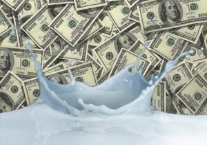 milk splashes in front of stacks of money