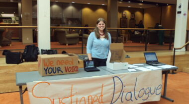 a woman stands in front of an SD table