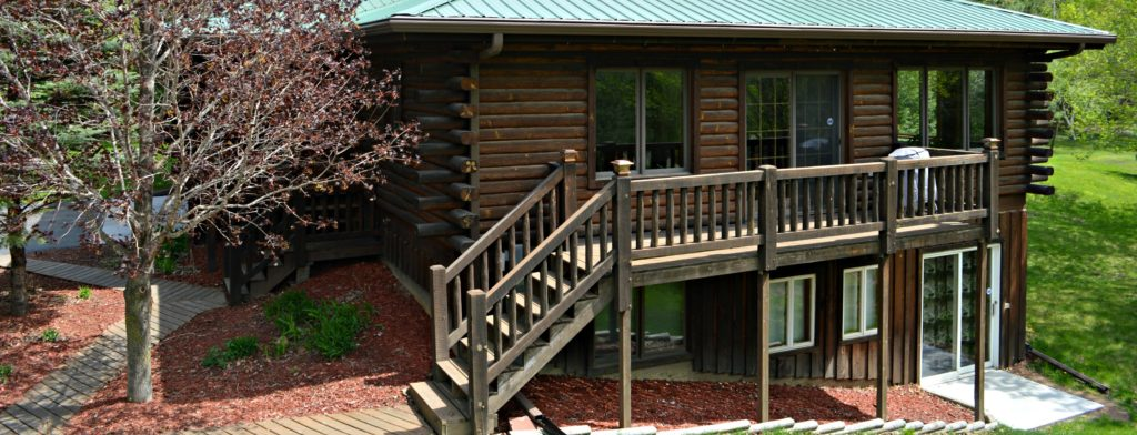 Log home with deck and green metal roof