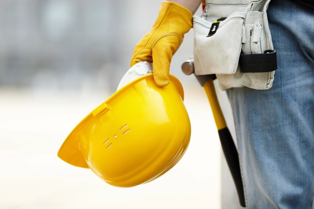 Construction worker holding yellow hardhat