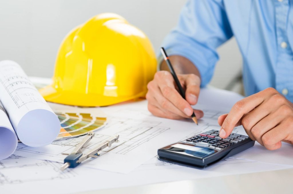 construction worker calculating blueprint scale