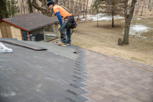 man inspecting roof during shingle installation